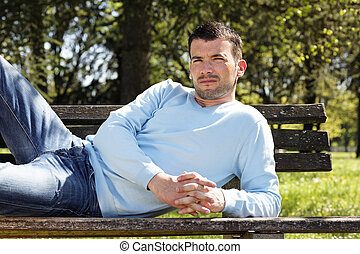 relaxed man on  a bench in a park