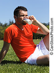 man in a park drinking milk after sport