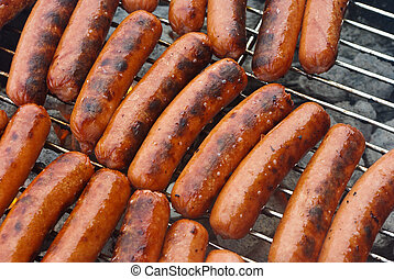 Hot Dogs on a Charcoal BBQ Grill - All beef hot dogs on...