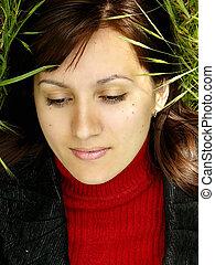 Beautiful face lies in grass