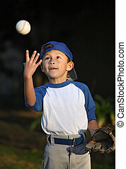 Young Boy Catching Baseball - Happy smiling young latino boy...