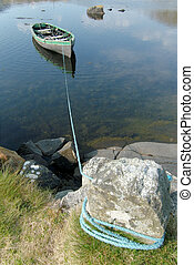 Rowboat - Small rowboat on a lake tied to the shore