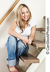 Young woman sitting on steps - Pretty young smiling woman...