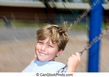 Swinging for fun - Kid playing on a school's swingset during...