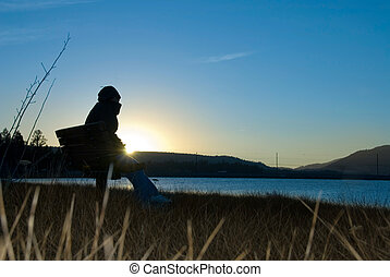 Solitude - A woman sits in solitude along a remote lakefront...