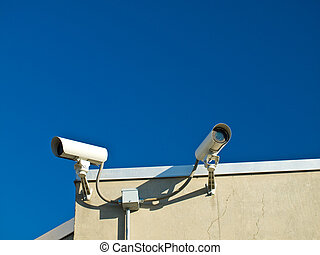 Security Cameras Performing Surveillance on the Side of a...