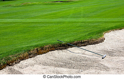 Sand trap - A rake sitting in a sand trap on a golf course