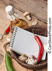 notebook for cooking recipes and vegetables on  cutting board