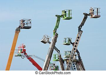 boom lifts - several colored boom lifts with cages