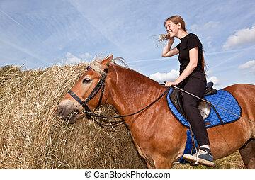 Yummy Hay - Girl feeding a horse in a field