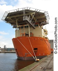 Orange ship tied up. - An orange offshore support vessel...
