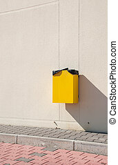 Garbage can - yellow garbage can hanging on wall at a urban...