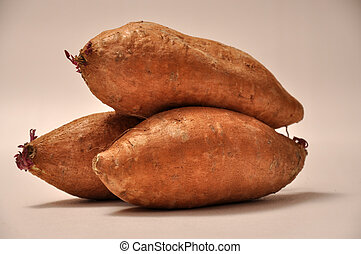 Sweet Potatos - A group of three sweet potatos on a white...