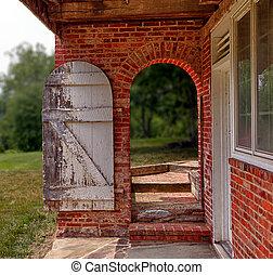 Open wooden door in brick wall to garden - Ancient white...