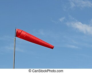 Bright red windsock blowing in the breeze with a bright blue...