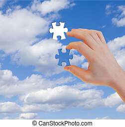 Human hand with last puzzle piece