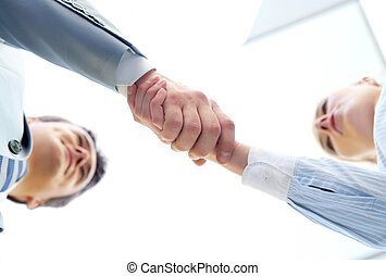 Congrats - Below angle of successful associates handshaking...