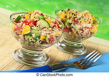 Delicious vegetarian quinoa salad in glass bowls with bell...