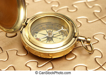 Golden Compass and Puzzle Concept - A brass compass rest on...