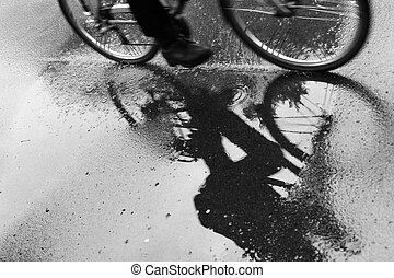 cyclist reflected in puddle in the rain