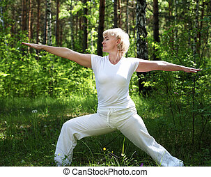 An elderly woman practices yoga in nature. The symbol of...
