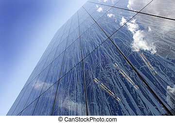 Glass facade of modern building with reflecting clouds