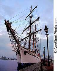 Sailboat Docked at Sunset - A vintage tall ship is docked in...