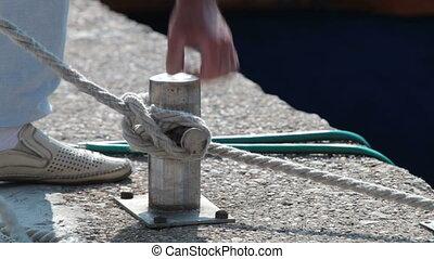 man tying mooring rope to bollard