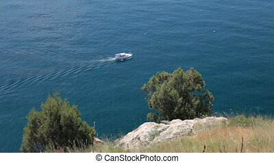 motorboat sailing along seashore - motorboat sailing along...