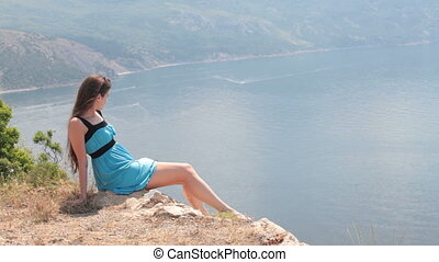 woman sitting on edge of cliff - young woman sitting on the...