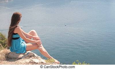 woman at  cliff - woman resting on a rock by the sea