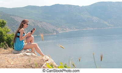 young woman reading e-book while sitting on top of a cliff...