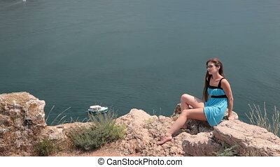 young woman resting on the cliff - young woman Resting on...