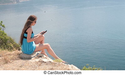 woman reading e-book - young woman reading e-book while...
