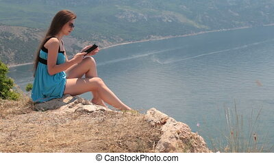 reading the e-book - young woman in a short blue dress...