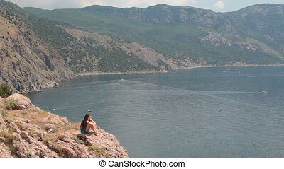 young woman Resting on  cliff near