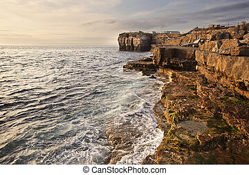 Waves crashing over rock formation cliffs at sunset with...