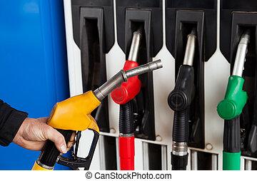 Gasoline station fuel pumps - Human hand holding gasoline...
