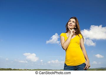 Happy woman thinking - Outdoor portrait of a beautiful and...