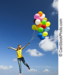 Flying with balloons - Happy young woman holding colorful...