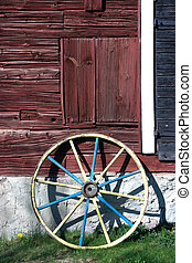 Wagon wheel - Painted wagon wheel against a red wall