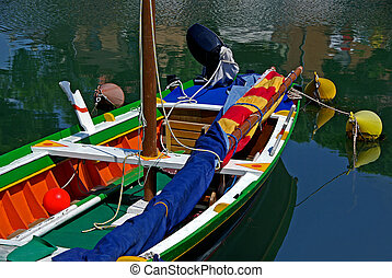 Colourful boat - Multicoloured boat with pole and outboard...