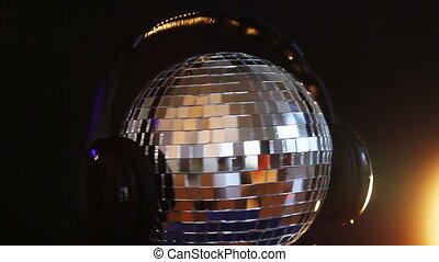 Rotating disco ball with headphones on top