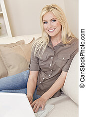 Young Blond Woman Using Laptop Computer At Home on Sofa -...