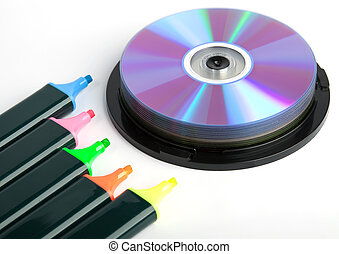 Colored markers and spindel of compact disks over white...