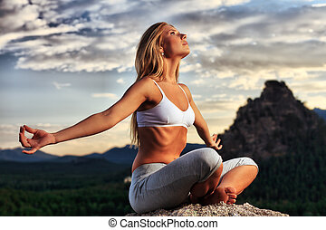 breathing - Slender young woman doing yoga exercise outdoors...