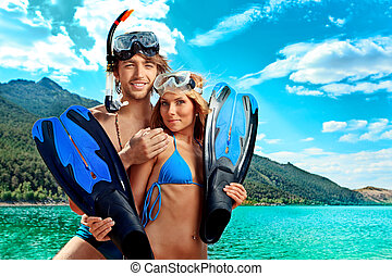 swimming - Happy young couple with snorkelling gear standing...