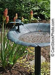 Bird Bath - A bird bath sets in this flower garden