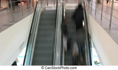People lifting on escalator in supermarket, top-down view,...