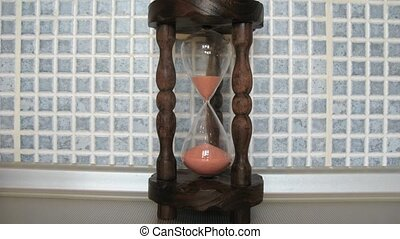 Front view on wooden sandglass running, time lapse